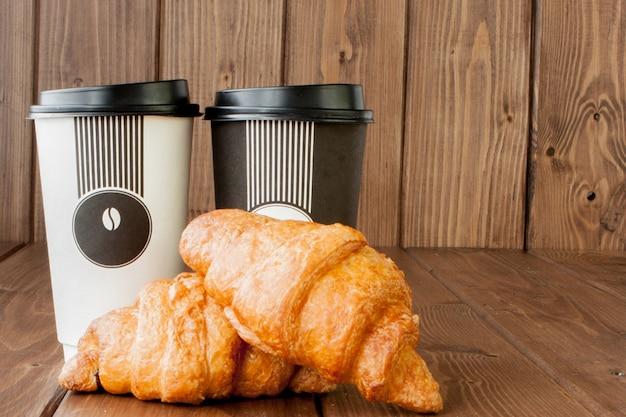Taza de café de papel y croissants sobre fondo de madera