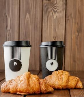 Taza de café de papel y croissants