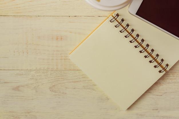 Taza de café de papel desechable, portátil y teléfono inteligente blanco con espacio de copia