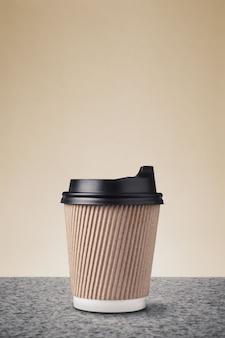 Taza de café de papel para llevar en blanco con tapas negras en la superficie de mármol contra la pared beige.