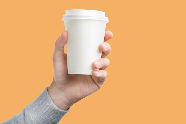 Una taza de café de papel en la mano. libro blanco taza de café en mano aislado