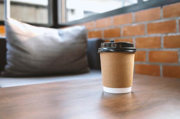 Taza de café de papel en la mesa en caf