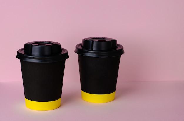 Taza de café de papel negro con una tapa sobre fondo rosa pastel.