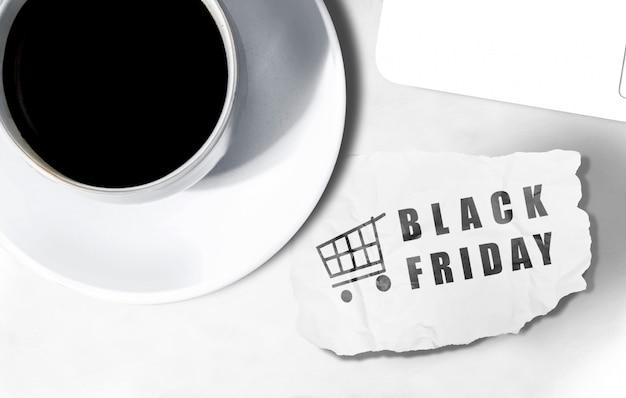 Taza de café y papel rasgado con texto de black friday en el escritorio