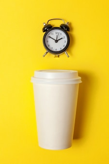 Taza de café de papel y reloj despertador sobre fondo amarillo