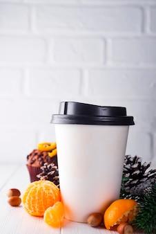 Taza de café de papel rodeada de adornos navideños.