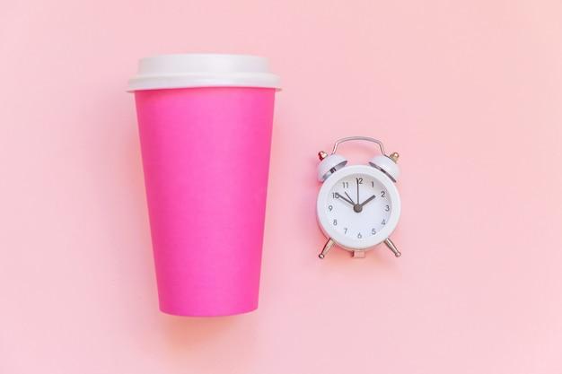 Taza de café de papel rosa de diseño laico simplemente plano y reloj despertador aislado sobre fondo colorido pastel rosa