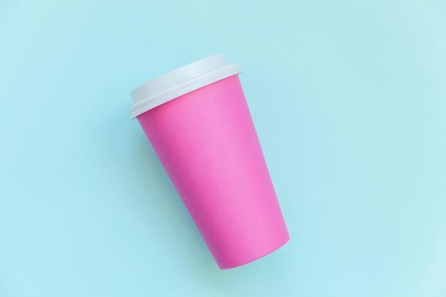 Taza de café de papel rosa de diseño simplemente plano sobre fondo de moda colorido pastel azul