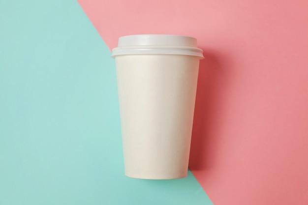 Taza de café de papel sobre fondo azul y rosa
