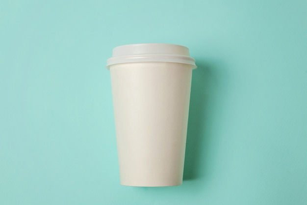 Taza de café de papel sobre fondo azul.
