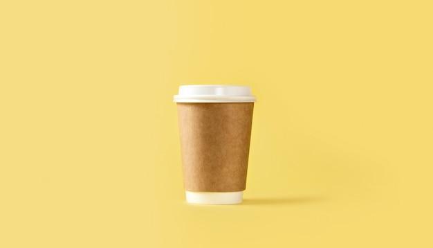 Taza de café de papel con tapa blanca sobre fondo amarillo