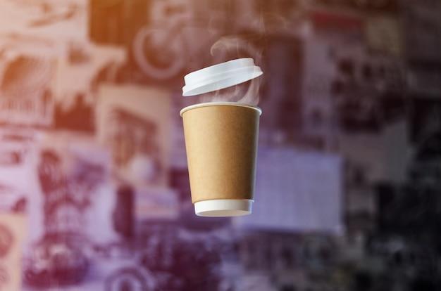 Una taza de café de papel con tapa de plástico levita