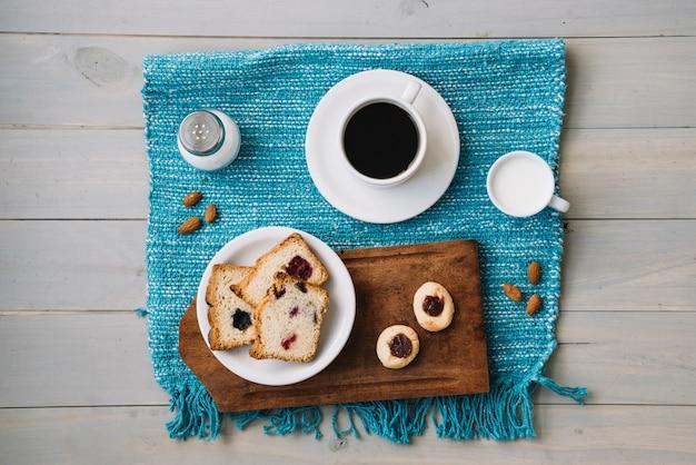 Taza de café y pastel con mermelada en la mesa