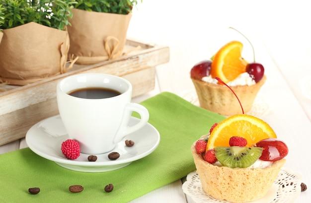 Taza de café y pasteles dulces con frutas en la mesa de madera
