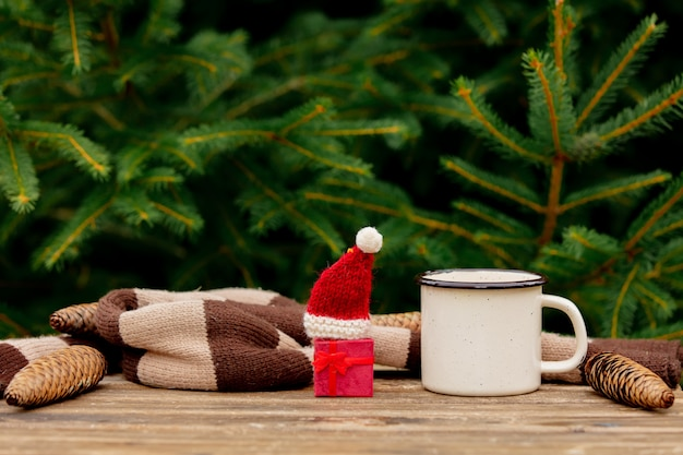 Taza de café y un pequeño regalo de navidad con sombrero en la mesa de madera con ramas de abeto en el fondo