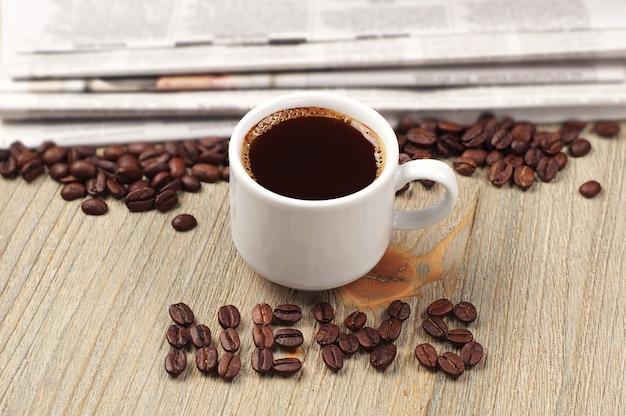 Taza de café, periódico y noticias de la palabra.