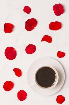 Taza de café y pétalos de rosa