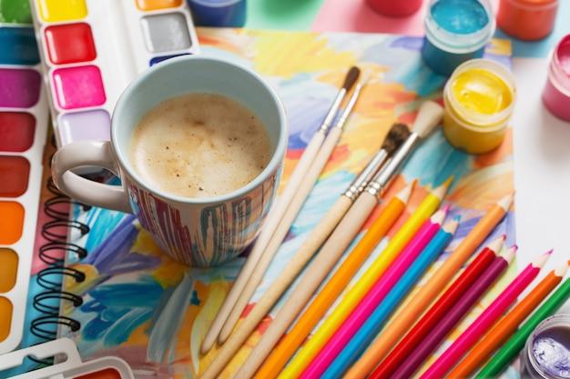 Taza de café y pinturas, lápices sobre fondo blanco.