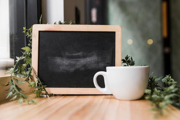 Taza de café con pizarra negra sobre superficie de madera