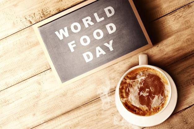 La taza de café y pizarra con texto del día mundial de la alimentación en madera