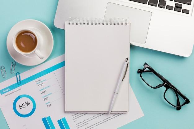 Taza de café, plan de presupuesto, bloc de notas en espiral, bolígrafo, lentes y computadora portátil sobre fondo azul