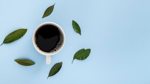 Taza de café plana y hojas con espacio de copia