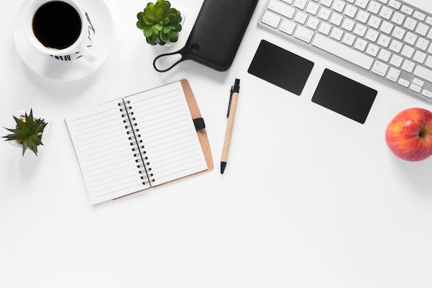 Taza de café; planta de cactus; tarjeta; manzana; diario y bolígrafo sobre fondo blanco