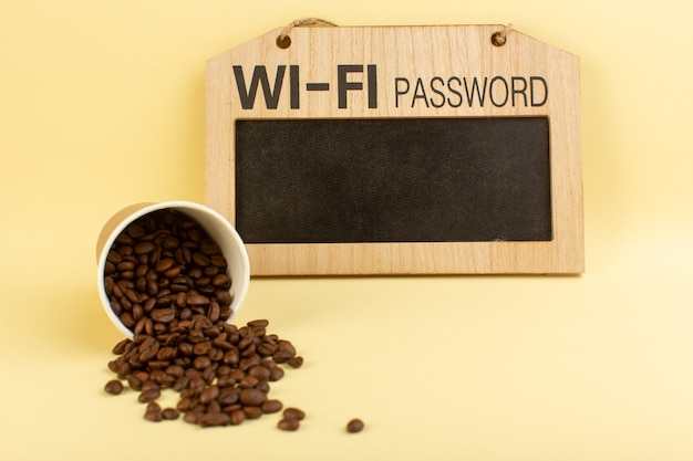 Una taza de café de plástico vista frontal con semillas de café marrón en la pared amarilla