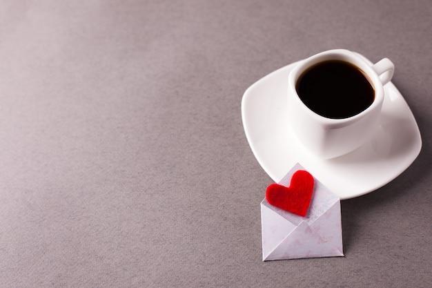 Una taza de café en un platillo y un corazón rojo