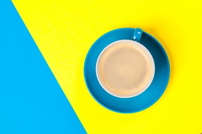 Taza de café y platillo sobre fondo de color