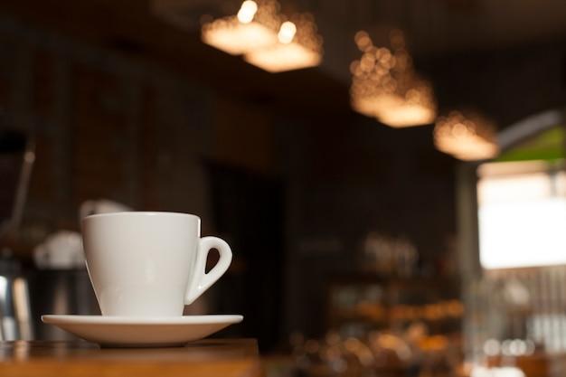 Taza de café con el platillo en la tabla con el fondo del café del desenfoque
