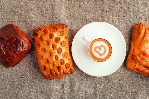 Una taza de café en un platillo y tortas en una fila en un centrico gris