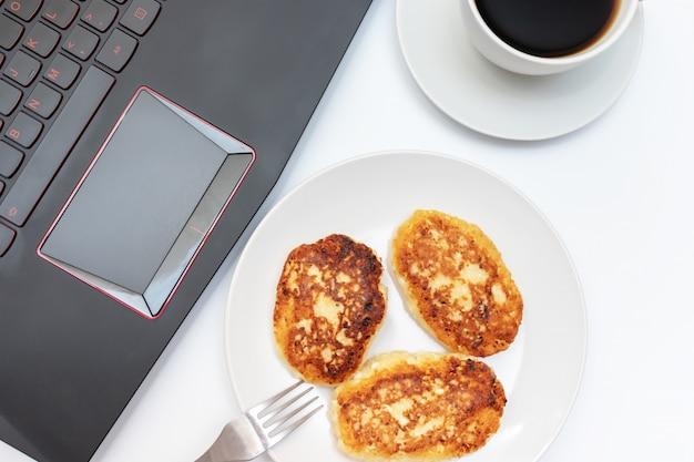 Taza de café y un plato con cuajada, panqueques de requesón para el desayuno en la mesa cerca de la computadora portátil