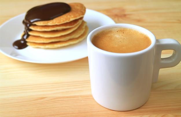 Taza de café y un plato de panqueques con salsa de chocolate belga