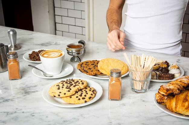 Taza de café y platos de galletas en el mostrador