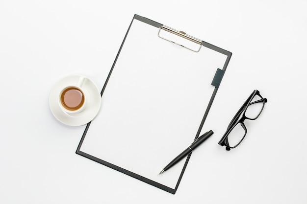 Taza de café y pluma con papel blanco en el portapapeles contra el escritorio de oficina
