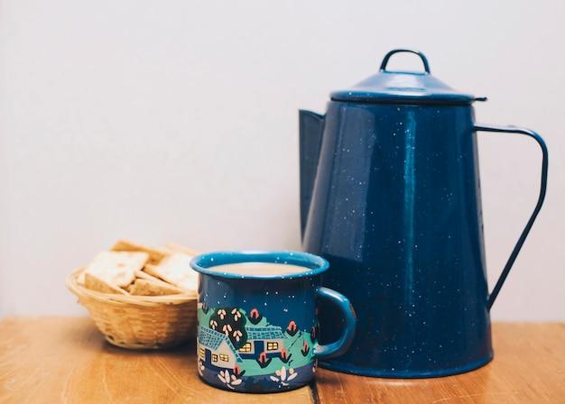 Taza de café y porcelana azul oscuro con galletas en el escritorio contra la pared