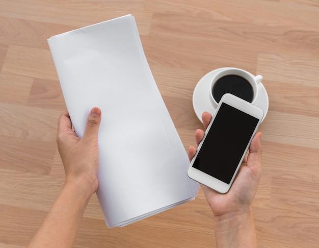 Taza de café con portátil y una mano con un papel