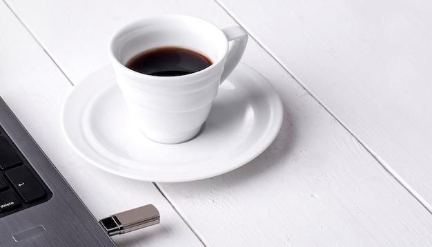 La taza de café y un portátil en la mesa de madera blanca
