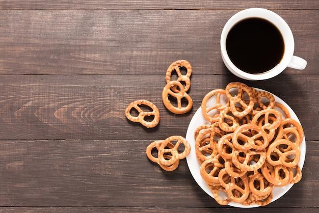 Taza de café con pretzels sobre fondo de madera