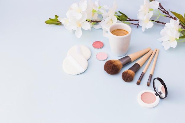 Taza de café con producto de cosméticos y ramita de flor blanca sobre fondo blanco
