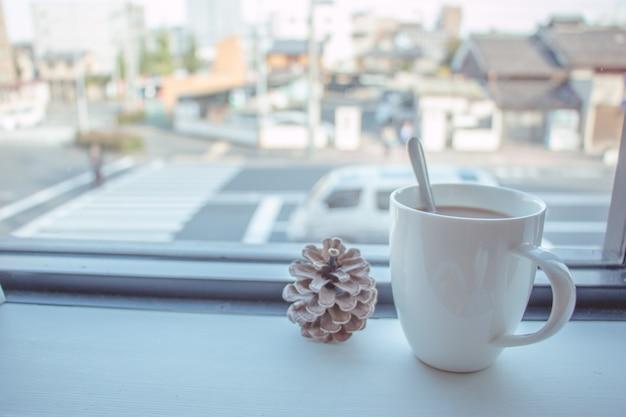 Taza de café puesta en barra de madera en la ventana de la tienda offee