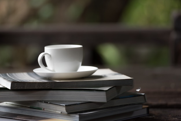Taza de café puesta en la pila de libros en la mañana.