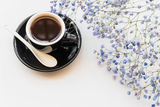 Taza de café y ramas de flor azul