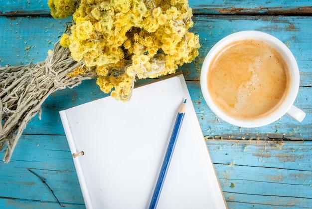 Taza de café con un ramo de flores silvestres secas