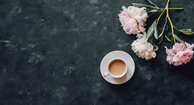 Taza de café con un ramo de peonías sobre un fondo oscuro
