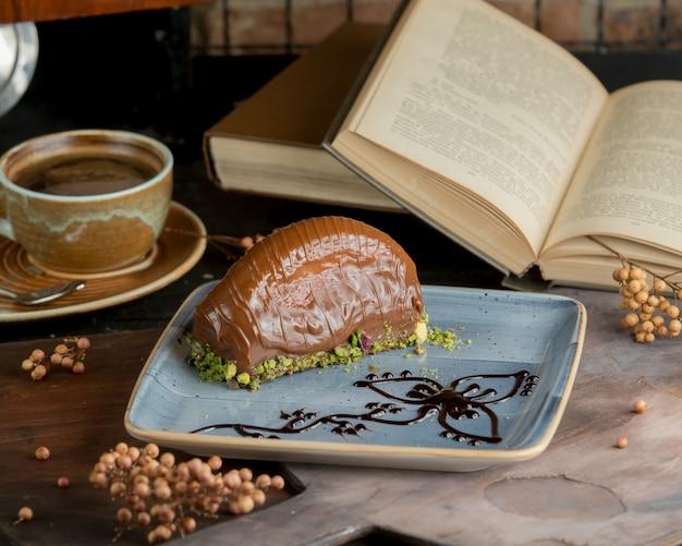 Una taza de café, una rebanada de pastel de chocolate y un libro.