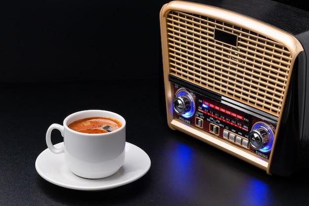 Taza de café y receptor de radio sobre fondo negro