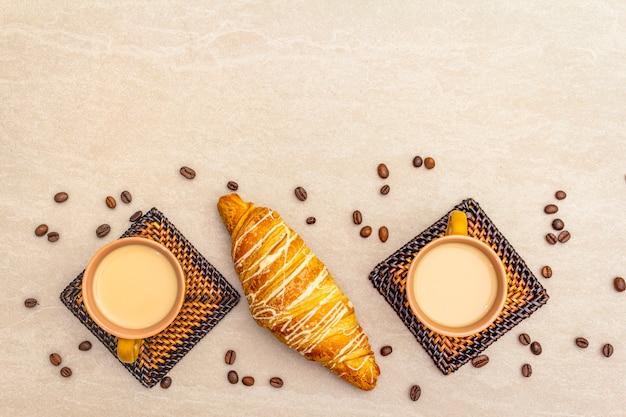 Una taza de café recién hecho con croissant. el concepto sobre una superficie de piedra con granos de café tostado y posavasos de mimbre, vista superior, espacio de copia, plano.