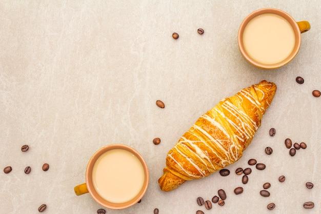 Una taza de café recién hecho con croissant. el concepto sobre una superficie de piedra con granos de café tostados, vista superior, endecha plana.